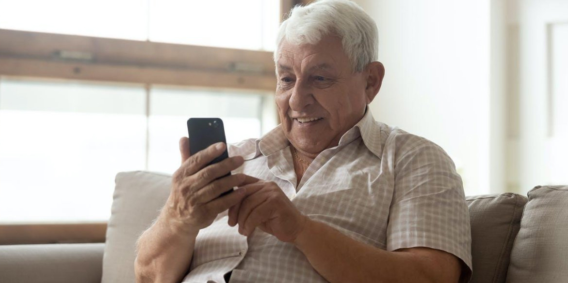 Elderly man checking cell phone