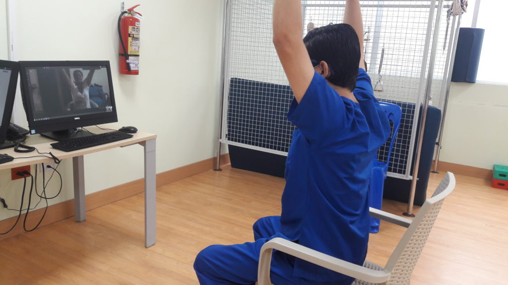 Person doing exercise with instructor on screen